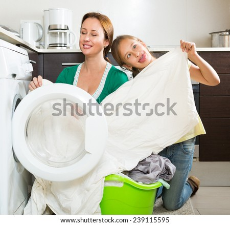 Home family laundry. Mother with playful daughter loading clothes into washing machine in kitchen - stock photo