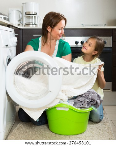 Home family laundry. Smiling mother with little daughter loading clothes into washing machine in kitchen. Focus on woman - stock photo