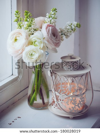 Home festive decorations, elegant bouquet of flowers, buttercups and white lilac and candle lantern on white vintage windowsill - stock photo