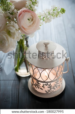 Home festive wedding decor, exquisite bouquet of flowers, buttercups and white lilacs, and lantern candle on a dark wooden board - stock photo