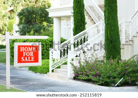Home for sale Real estate sign in front of new house - stock photo