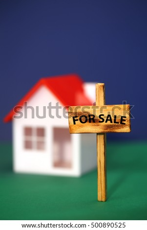 Home for sale sign in front of house model, shallow field of focus