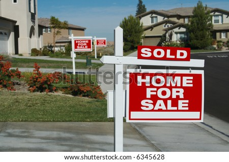 Home For Sale Signs & One Sold in Front of Beautiful New Homes. - stock photo
