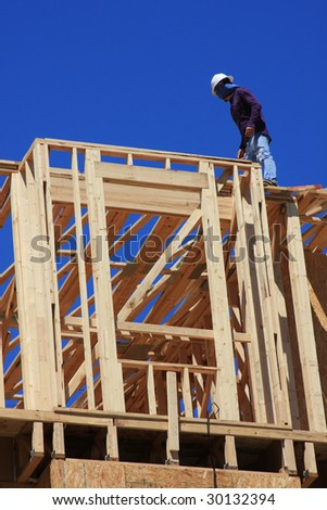 Home frame with construction worker present on structure - stock photo
