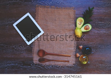 Home furnishings in the kitchen, handmade linen towel near modern tablet of last generation that next to a beautifully laid wooden cutlery and avocado salad for a light dressing of soy sauce - stock photo
