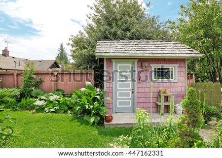 Home garden on backyard with small red barn shed and red wooden fence - stock photo