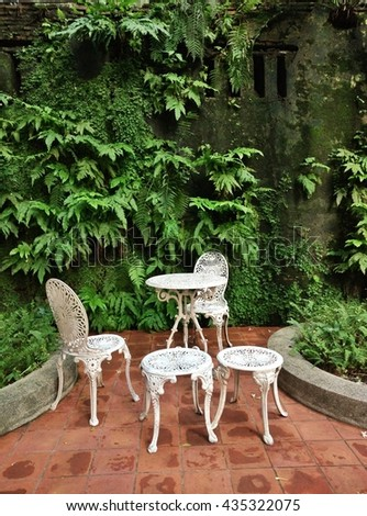 home garden with a set of chairs and table, green wall background