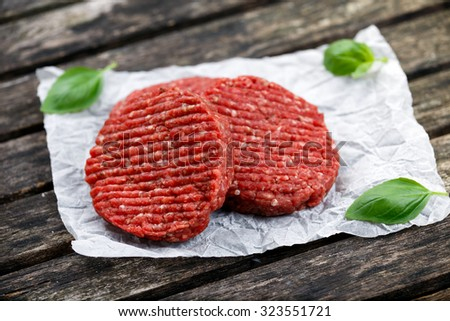 Home HandMade Minced Beef burgers decorated with Basil. on crumpled paper. wooden table. - stock photo