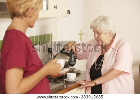 Home Help Sharing Cup Of Tea With Senior Woman In Kitchen