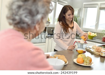 Home helper serving breakfast to elderly woman - stock photo