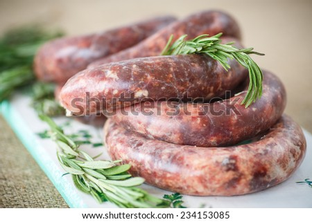 home hepatic raw sausage with rosemary on a table - stock photo