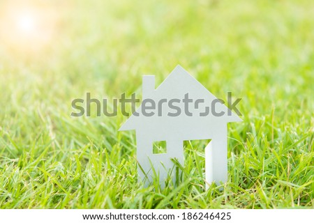 Home, House white paper cut concept and sun light in green field background