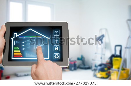 home, housing, people and technology concept - close up of man hands pointing finger to tablet pc computer and regulating room temperature over storeroom or building background - stock photo