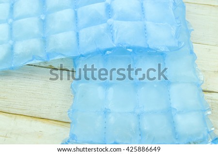Home ice made in cube bags on wooden background - stock photo