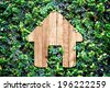 Home icon on green leaves wall,Eco home system. - stock photo
