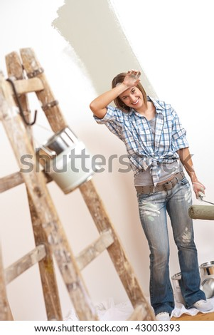Home improvement: Cheerful woman with paint roller and ladder painting wall