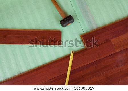 Home improvement construction laying stained brown wooden bamboo hardwood boards flooring and rubber mallet tool - stock photo