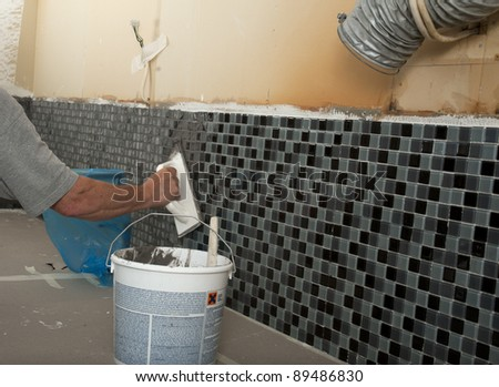 Home improvement - grouting mosaic tiles. - stock photo