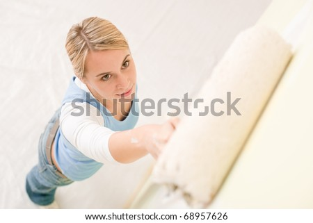 Home improvement - handywoman painting wall with roller - stock photo