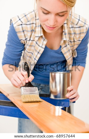 Home improvement - handywoman painting wooden plank in workshop - stock photo