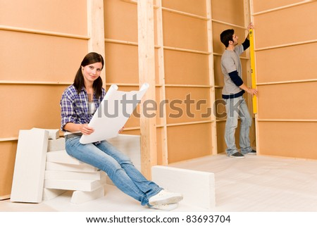Home improvement happy young couple with architectural blueprints fixing house