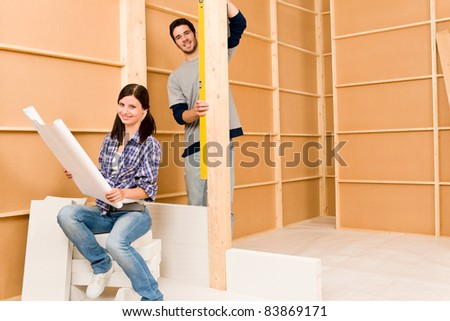 Home improvement happy young couple with architectural blueprints fixing house - stock photo