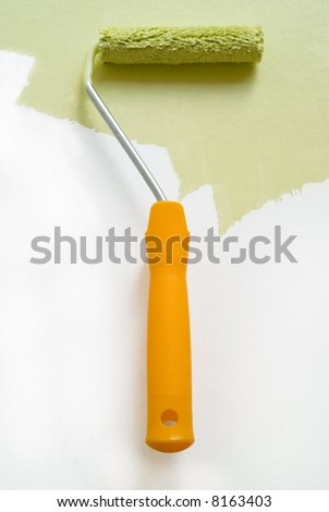 Home improvement paint and roller on white wall - stock photo
