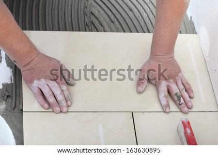 Home improvement, renovation - construction worker tiler is tiling, ceramic tile floor adhesive - stock photo