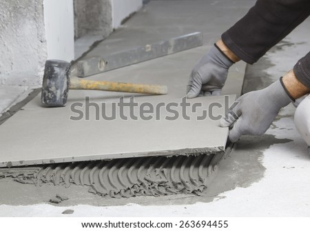 Home improvement, renovation - construction worker tiler is tiling, ceramic tile floor adhesive, trowel with mortar