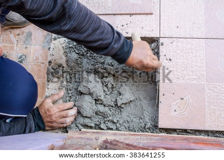 Home improvement, renovation - construction worker tiler is tiling, ceramic tile floor adhesive - stock photo