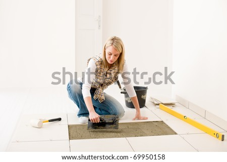 Home improvement, renovation - handy woman laying tile, trowel with mortar - stock photo
