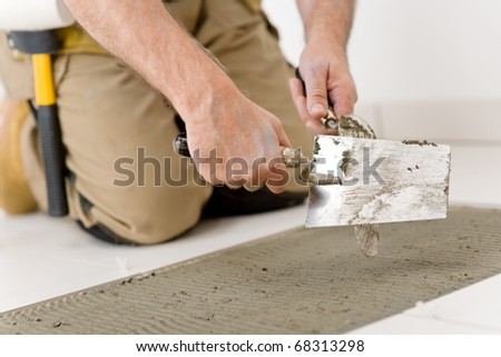 Home improvement, renovation - handyman laying tile, trowel with mortar - stock photo