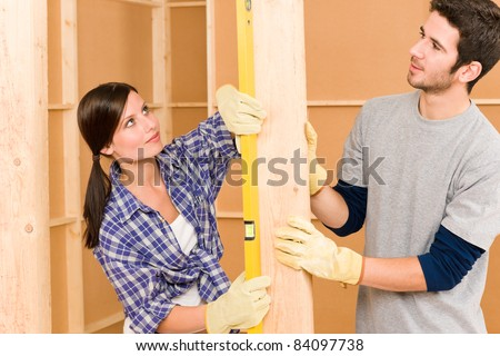 Home improvement smiling young couple fixing wall with spirit level - stock photo