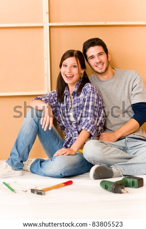 Home improvement young cheerful couple repair tool relax on floor - stock photo