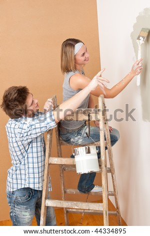 Home improvement: Young couple painting wall with paint brush - stock photo