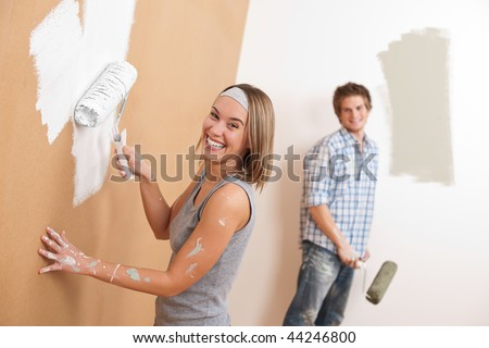 Home improvement: Young couple painting wall with paint roller - stock photo
