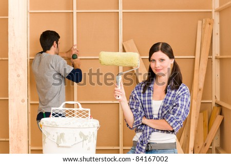 Home improvement: young happy couple fixing new house renovating wall - stock photo