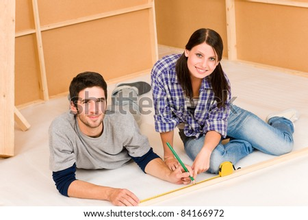 Home improvement young happy couple working on floor renovations
