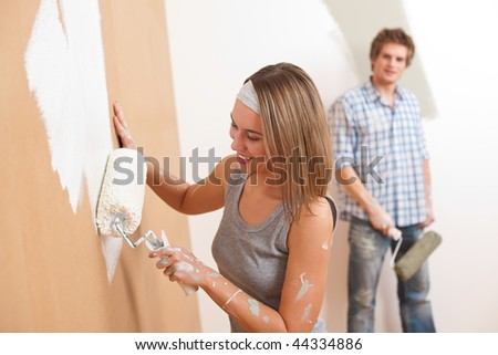 Home improvement: Young man and woman painting wall with paint roller - stock photo