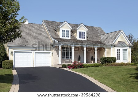 Home in suburbs with columns and double garage - stock photo