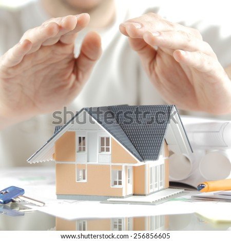 Home Insurance Concept - Close up Hands Covering Miniature Model House on the Table with Keys and Blueprints on the Sides. - stock photo
