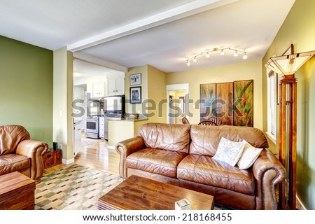 Home interior in yellow and green colors with brown leather couch and chair