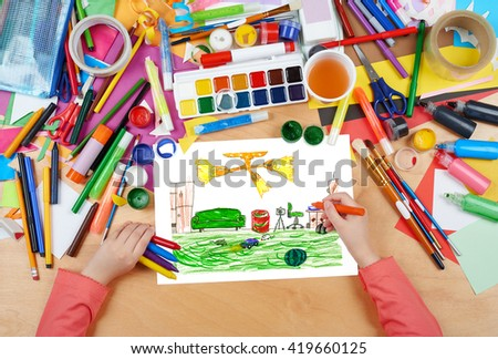 home interior, living room with toys, child drawing, top view hands with pencil painting picture on paper, artwork workplace - stock photo