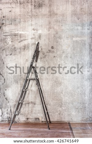 Home interior room repair concept - old gray concrete wall and dirty brown floor in repairing room with old dirty black stepladder near the wall closeup view  - stock photo
