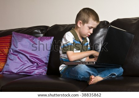 Home interior shot of a child sitting and using a laptop