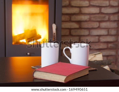 Home interior with fireplace, red book and tea on table - stock photo