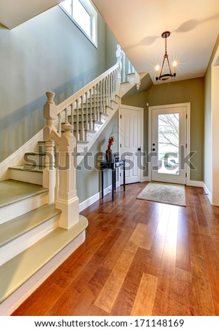 Home interior with green walls. Main hallway with staircase and cherry hardwood floor. - stock photo