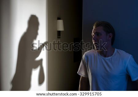 Home Invasion Concept - Frightened Homeowner Watches Thief - stock photo