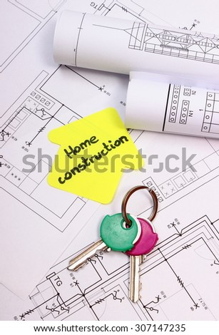 Home keys, house of yellow paper with text home construction and rolls of diagrams lying on electrical construction drawing of house, technology and concept of building home
