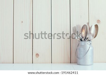 Home Kitchen Decor: vintage cutlery, spoons and forks in zinc can on a wooden board background , cozy arrangement retro style, soft pastel colors. - stock photo